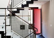 Bright red door and a sculptural steel staircase at the entrance of Noe Valley Residence 217x155 Noe Valley Residence: Modern Industrial Bachelor Pad Packed with Iconic Décor