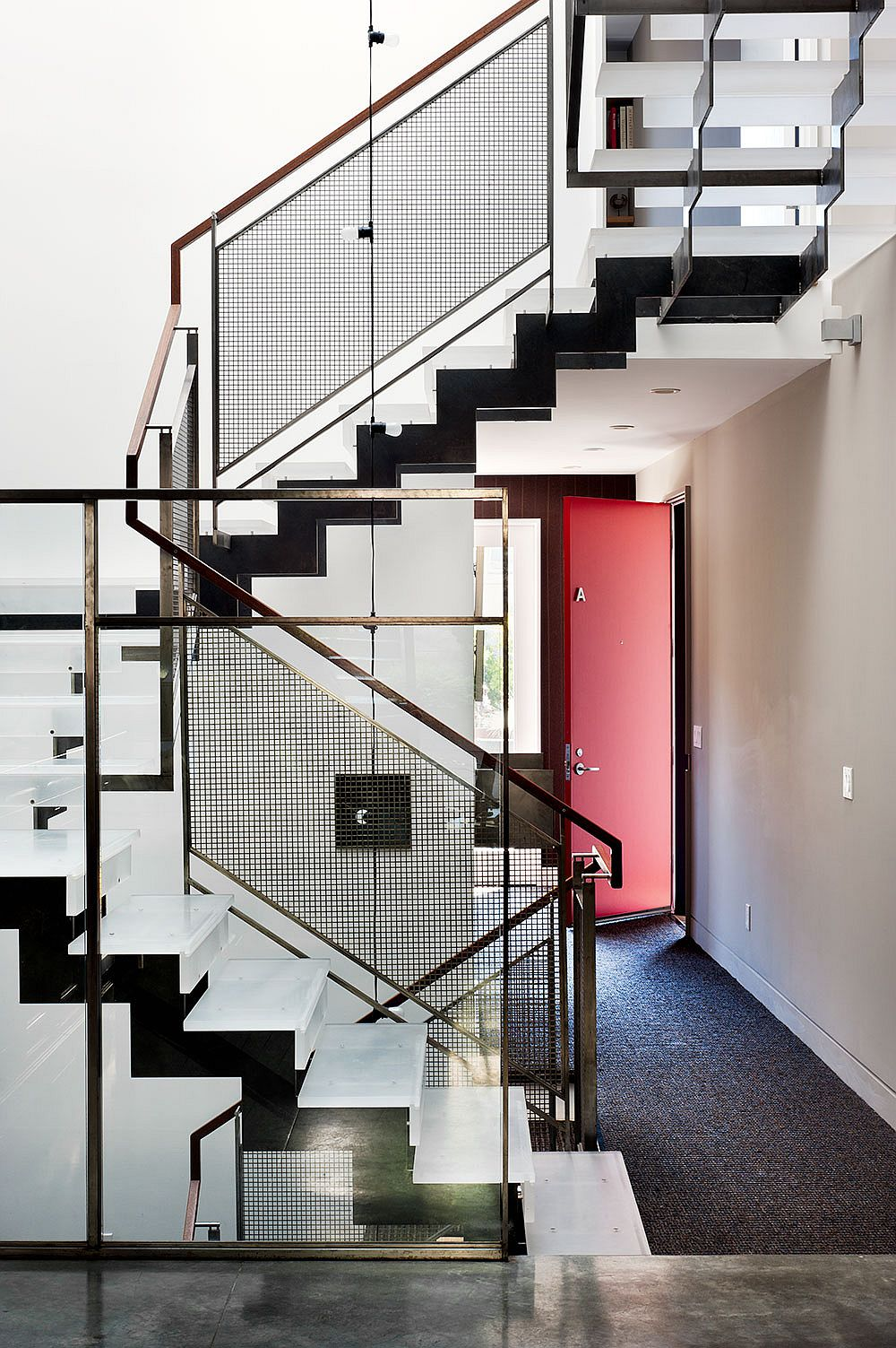 Bright red door and a sculptural steel staircase at the entrance of Noe Valley Residence