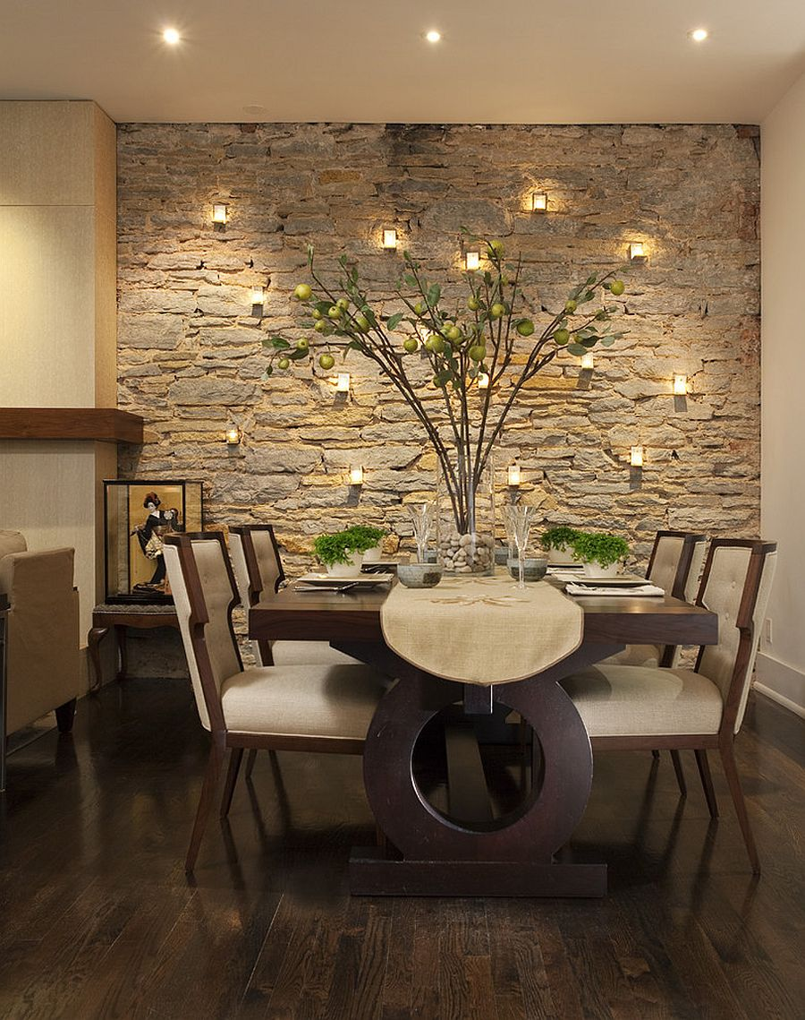 Candles highlight the beauty of the stone wall in the dining room [Design: Charlie & Co. Design]