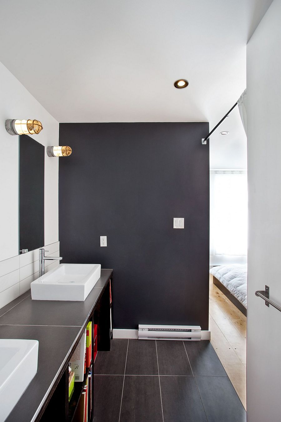 Dark bathroom connected with the white master bedroom provides visual contrast