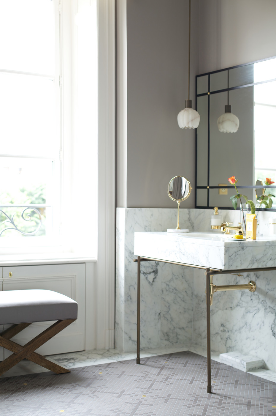 Delicate pendant lighting in a powder room with marble detailing