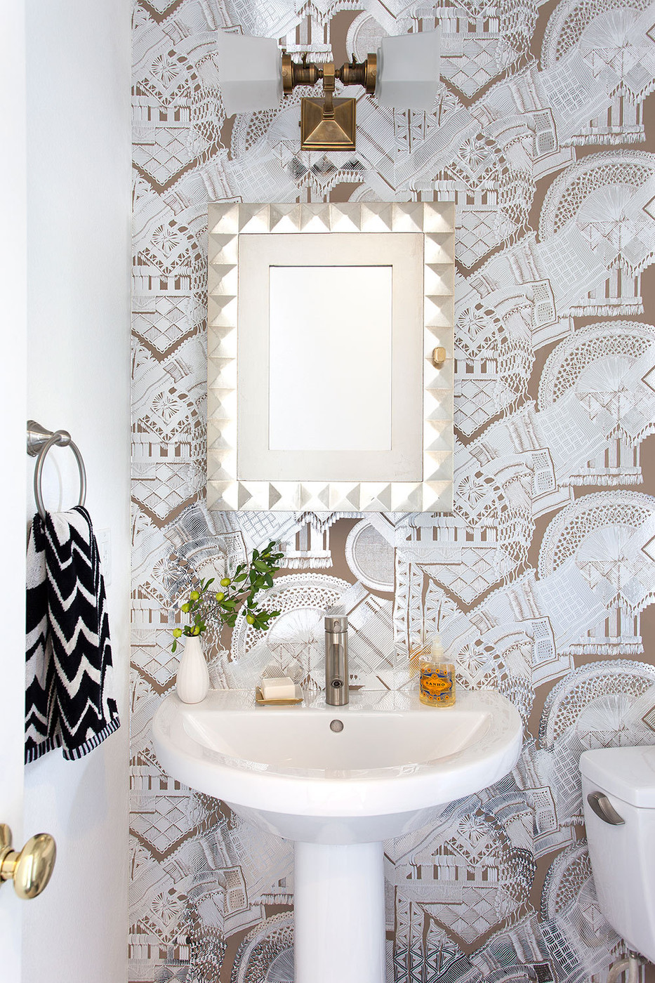 Eclectic bathroom with wallpaper and a geometric mirror