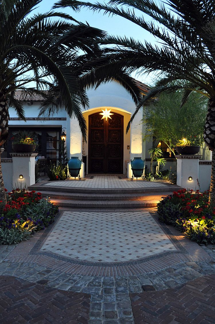 Entryway with arched date palms is the perfect way to lead into a Mediterranean home [Design: Exteriors By Chad Robert]