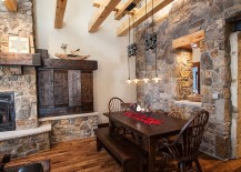 Farmhouse style dining room with wooden beams, stone walls and ingenious lighting