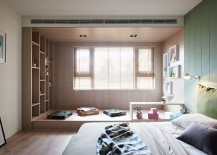 Floor cushions and an elevated wooden platfor create a simple reading zone in the bedroom