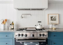 Gorgeous kitchen range in black stands out thanks to the neutral backdrop and blue cabinets