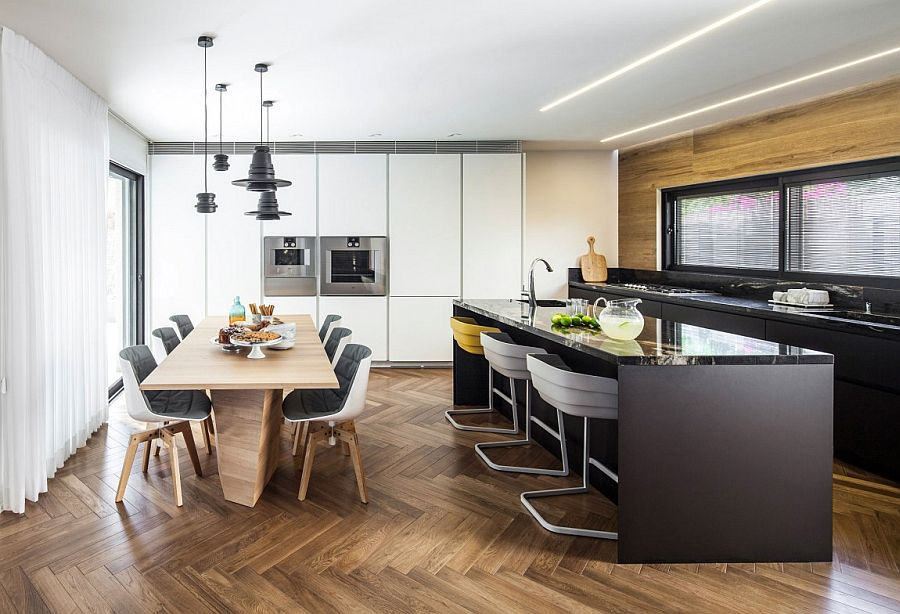 Herringbone flooring adds pattern to the neutral kitchen and dining