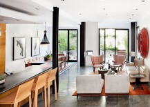 Iconic midcentury decor, creative artwork and industrial lighting shape the open plan living area