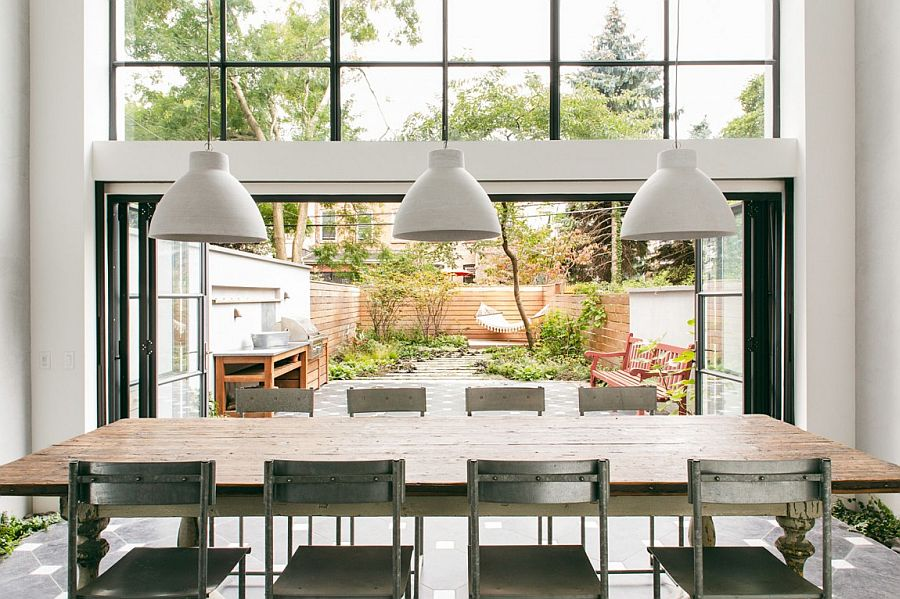 Large floding glass doors with black metal frame open up to bring the outdoors inside