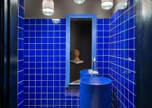 Massive industrial pipe turned into custom sink inside the small bathroom with bright blue walls