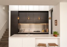 Modern kitchen with a series of brass pendants