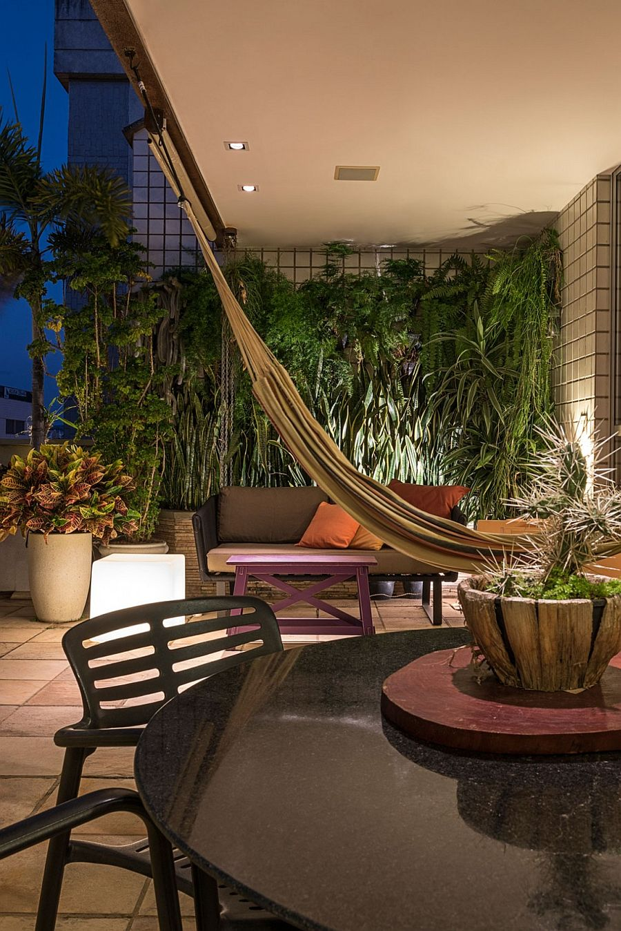 Natural greenery and hammock create an urban retreat on the top level of the penthouse