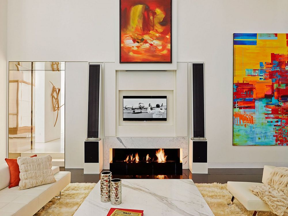 Sliding frames open up to reveal the hidden TV above fireplace
