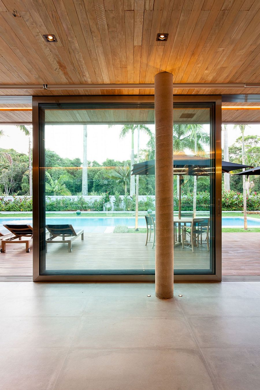 Sliding glass doors connect the pavilion with the pool area
