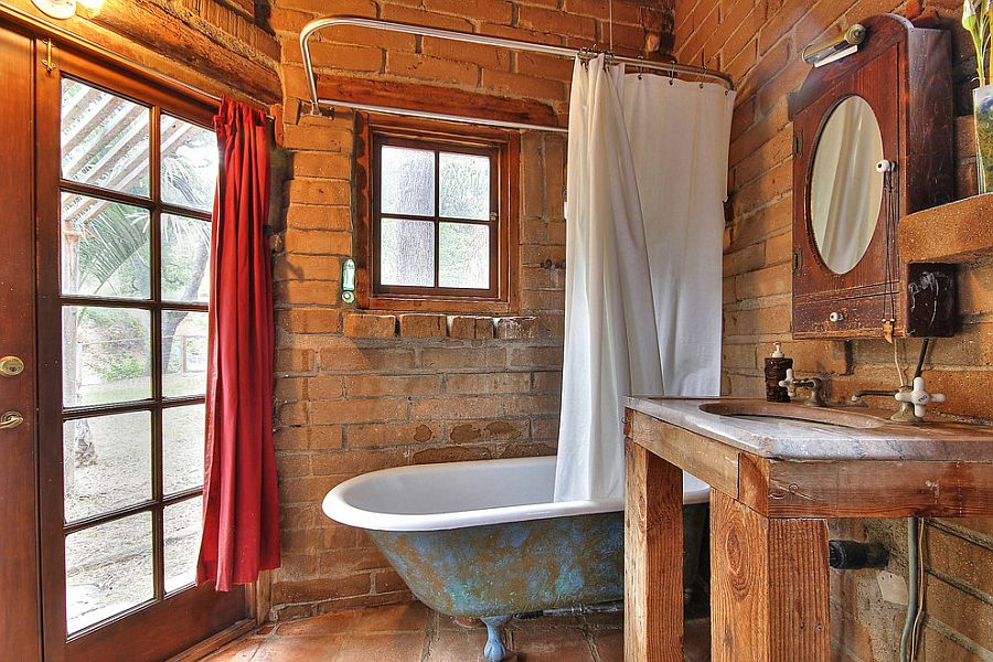 Small rustic bathroom with weathered bathtub and brick backdrop [From: Julie Angelos]
