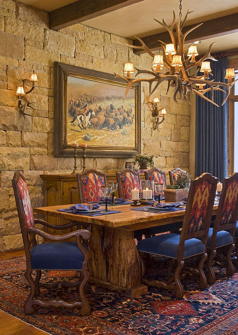 Stone wall and antler lighting for the rustic dining room [Design: Rick O'Donnell Architect]