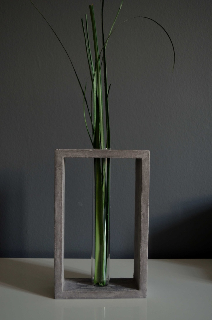 Transparent glass tube vase in grey concrete stand