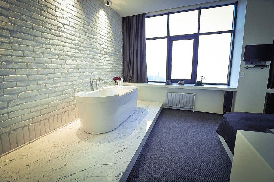 White brick wall fits in seamlessly with the contemporary vibe of the master bedroom with bathtub [Design: Anasayfa]