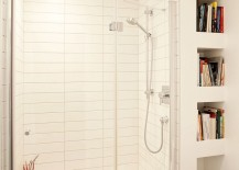 White shower area with small niches next to it that store books and magazines
