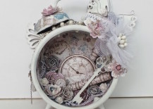 White vintage alarm clock with paper flowers and key inside