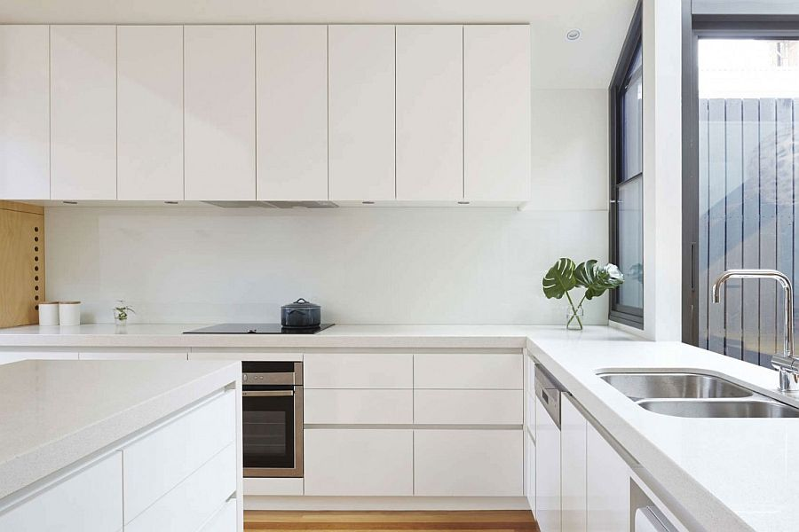 All-white contemporary kitchen with smart central island and ample cabinet space