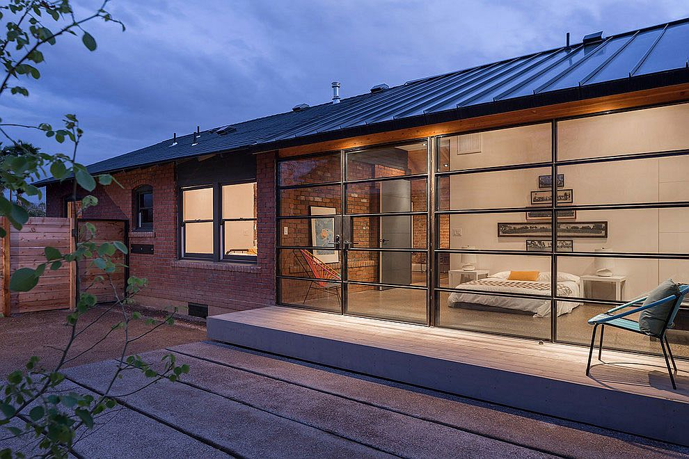 Contemporary glass and steel extension sits next to old brick, Carriage House in Phoenix