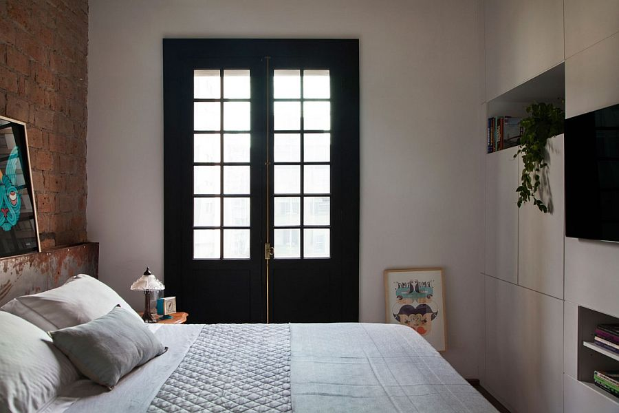 Dark window frames and exposed brick headboard wall style the small bedroom