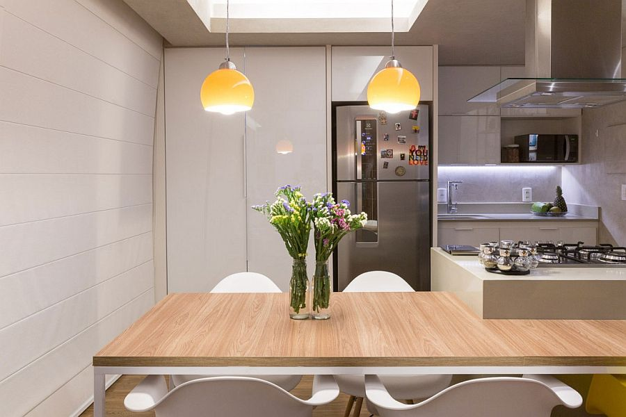 Dining table design is integrated with the kitchen island to save space