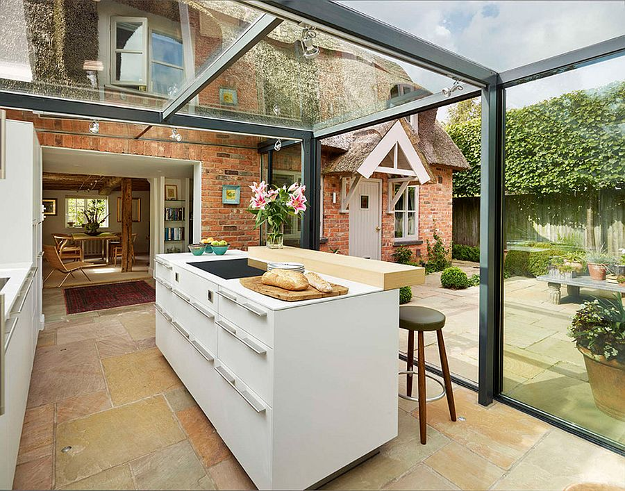 Glass box kitchen lets in natural light and illuminates the foyer indoors