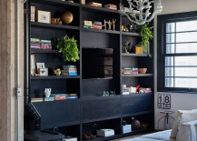 Large open bookshelf in dark wood anchors the light filled living room 217x155 Old World Charm Finds Modern Expression Inside Apartamento Jardins