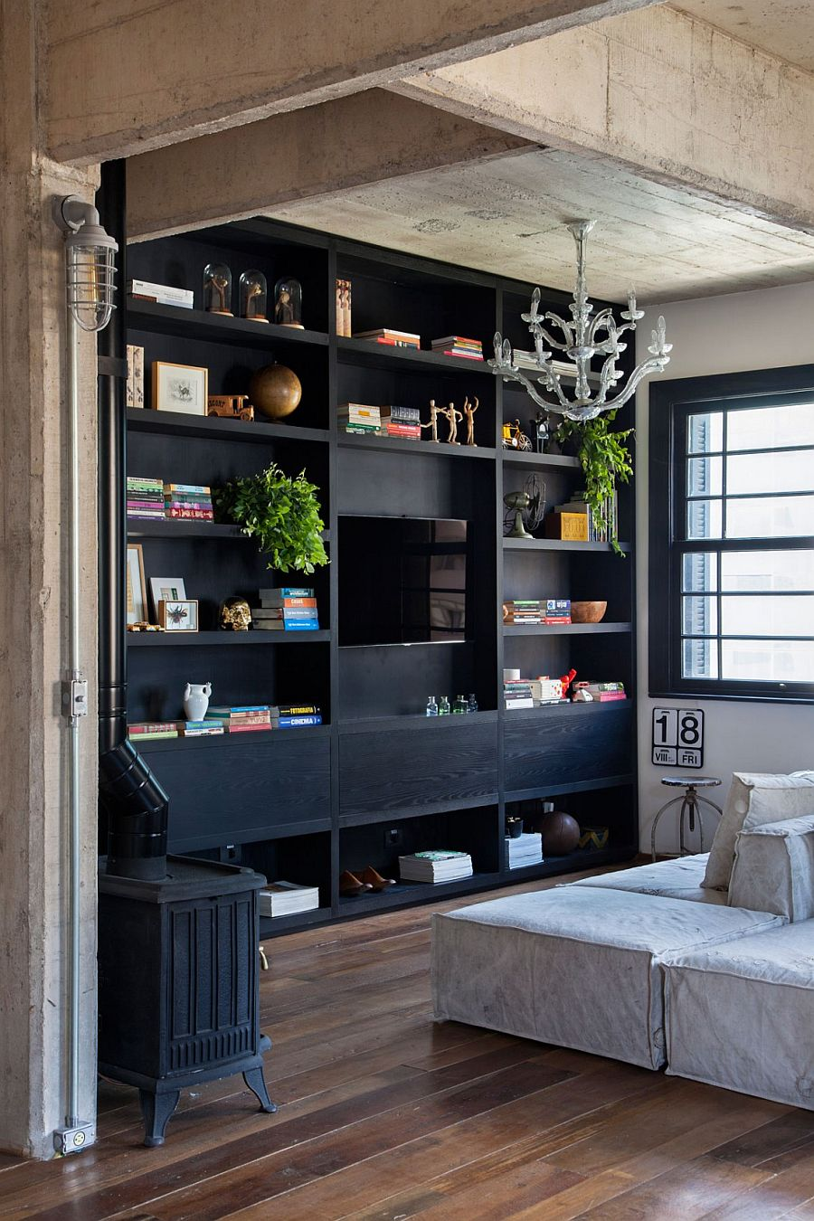 Large, open bookshelf in dark wood anchors the light-filled living room
