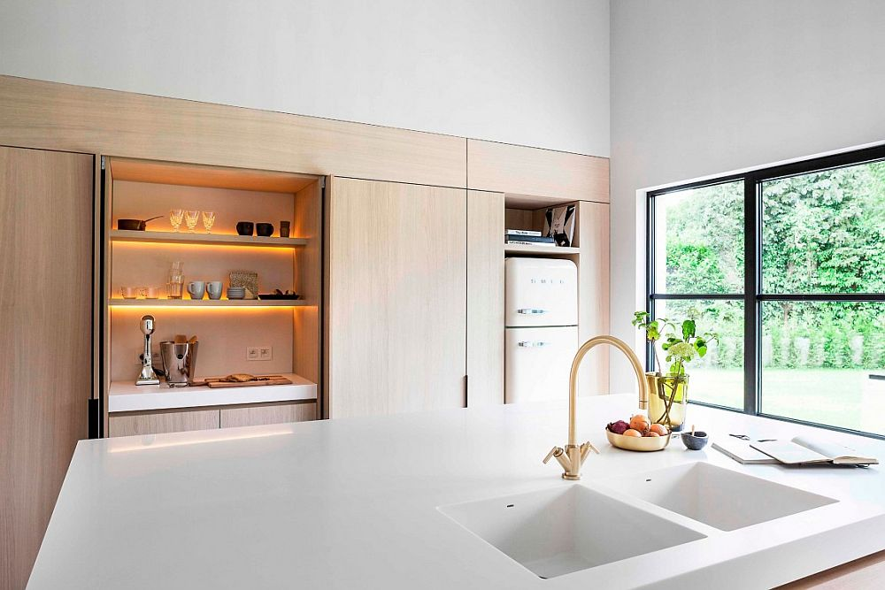 Large window with dark frame brings natural ventilation into the kitchen