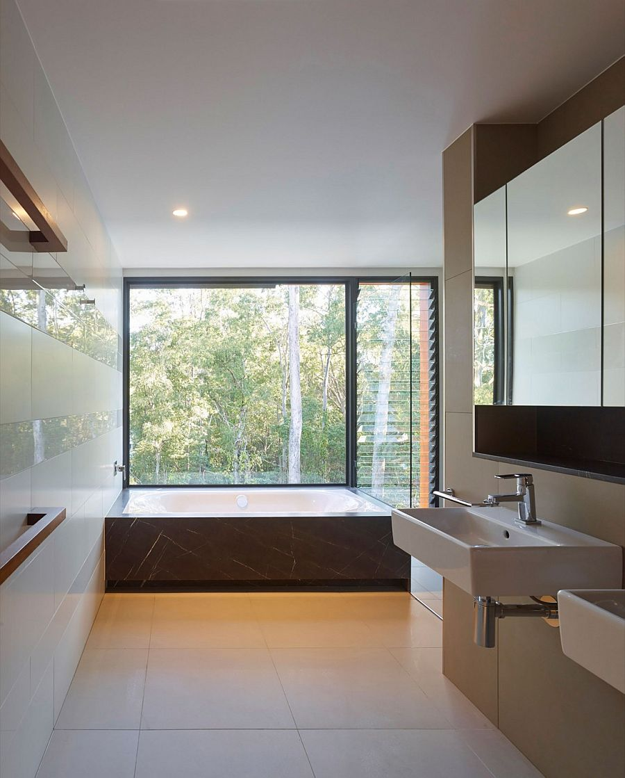 Luxurious contemporary master bath with lovely view of the landscape around it