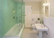 Mint tile shower in a wallpapered bathroom