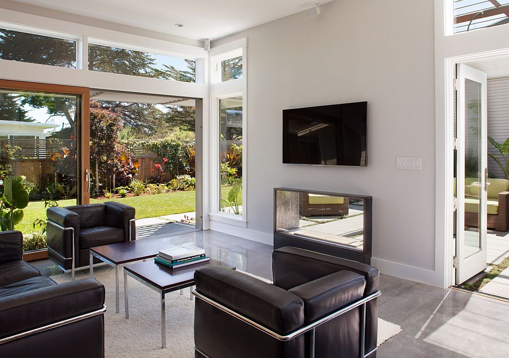 Open living room with sliding glass doors surrounded by the backyard