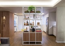 Open metallic shelf serves both the kitchen and living area
