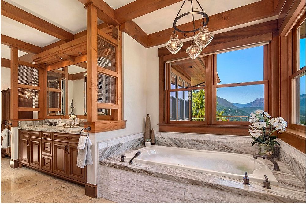 Rustic bathroom with stone bathtub and lovely mountain views [Design: Fine Design Interiors]