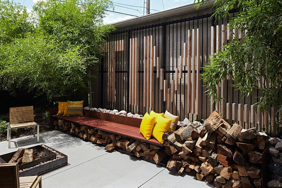 Small backyard with concrete deck and stacked firewood