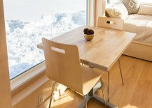 Small dining table and twin chairs next to the window inside the tiny home