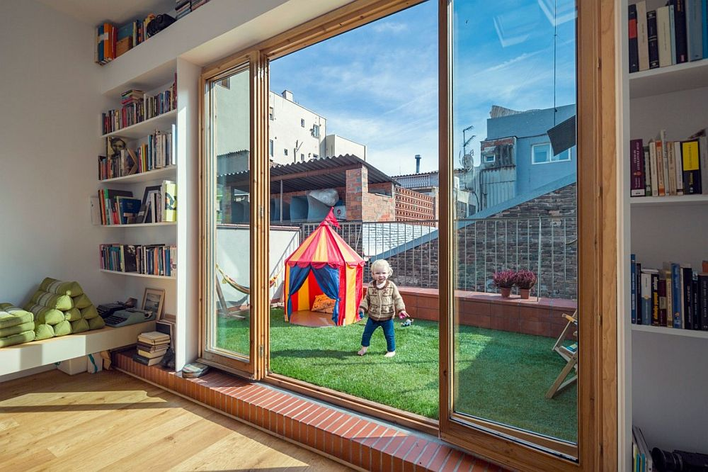 Small gardened terrace and kids' play area connected with home studio
