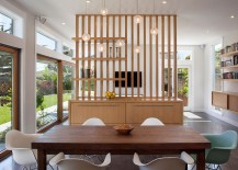 Smart cabinet design delineates the dining space from the living area
