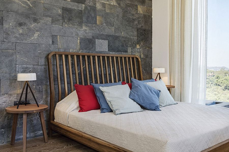Stone accent wall and woodsy bed for the Mediterranean bedroom