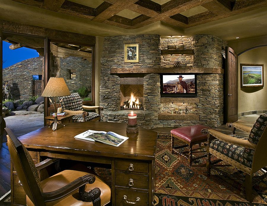 Stone wall with fireplace and TV becomes the showstopper in this home office [Design: Bess Jones Interiors]