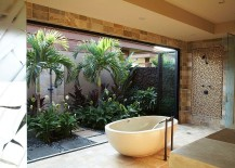 Tropical bathroom brings the outdoor garedn inside with folding glass doors