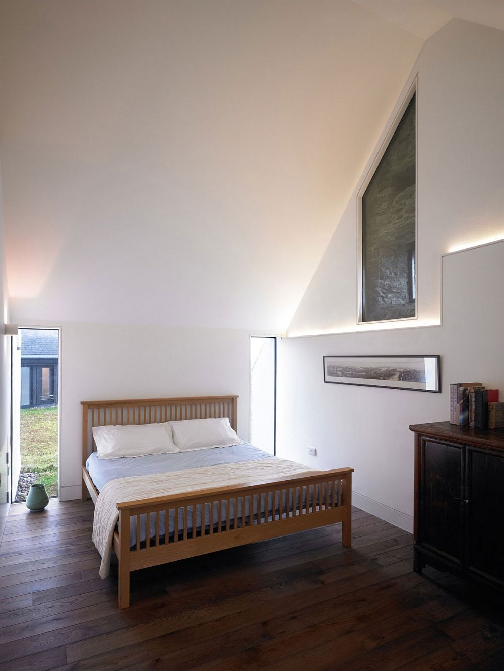 Two glass windows next to the bed usher in ample natural light