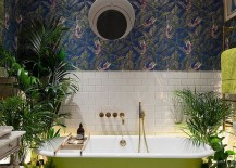 Wallpaper and plants create a jungle-inspired environment inside the eclectic bathroom