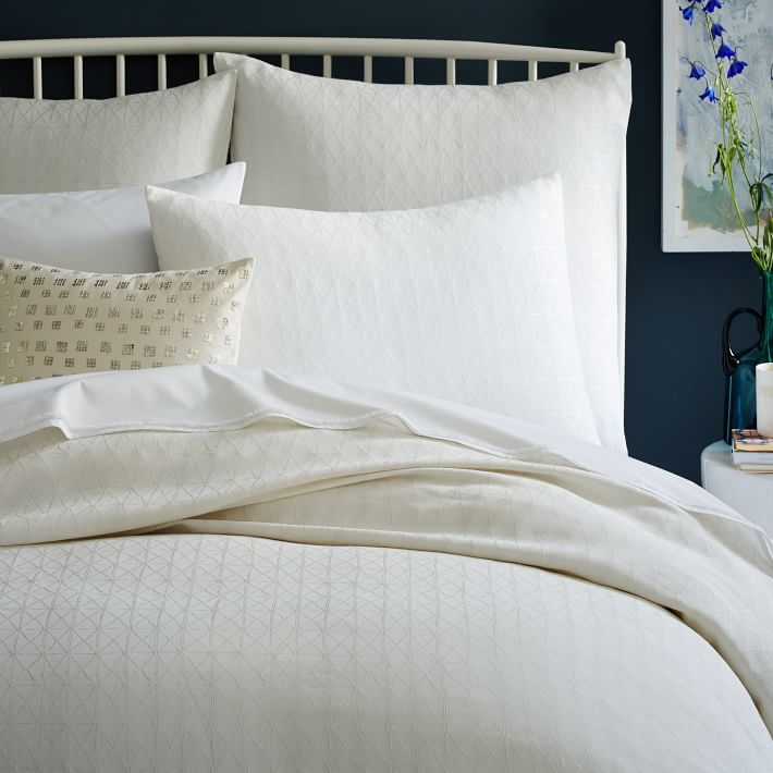 White bedding is a refreshing choice with dark walls