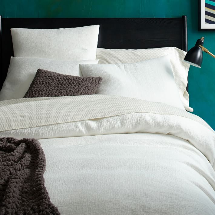 White bedding pops against a teal wall