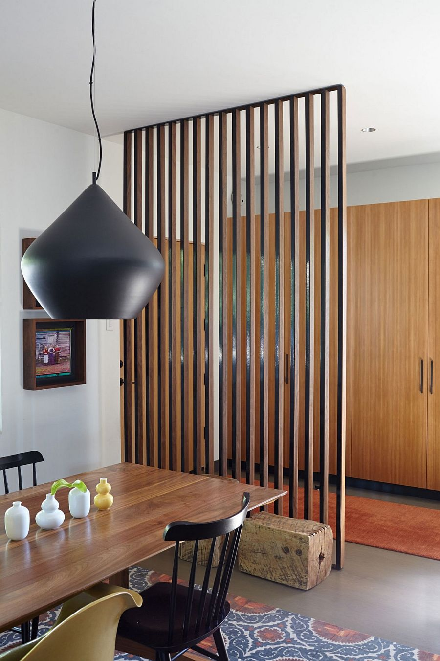 Wooden slats delineate the dining space from the living room