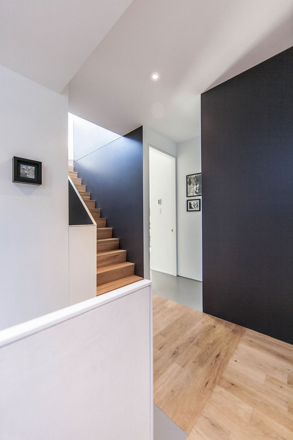 Wooden staircase and flooring bring a warmer texture to the interior
